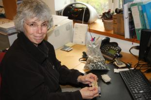 Sue in our offices putting backing-plates on the pin-badges (only 1999 left to go)!